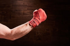 Boxer fist punch with red bandage on a wooden background. Stock Photography