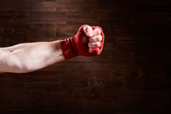 Boxer fist punch with red bandage on a wooden background. Royalty Free Stock Images