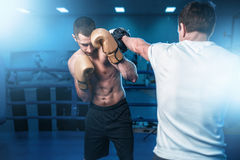 Boxer in gloves exercises with sparring partner Stock Photos