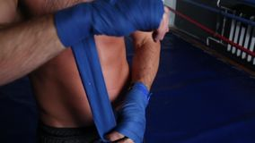 The boxer in the gym is wrapping up bandages. Close-up stock video footage