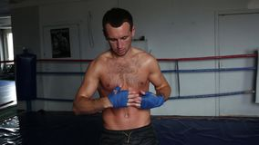 The boxer in the gym is wrapping up bandages. Boxer prepares for sparring stock video footage