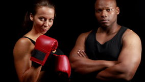 Boxer with her instructor posing for camera. Against black background stock video