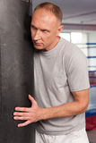 Boxer and his coach doing some punching with bag. Stock Images