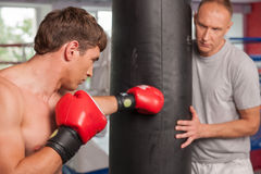 Boxer and his coach doing some punching with bag. Stock Photography