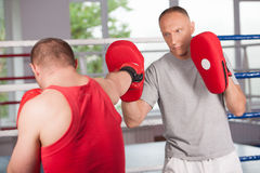 Boxer and his coach doing some sparring in ring Royalty Free Stock Photo