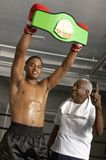 Boxer Holding Championship Belt. Portrait of a happy African American boxer holding championship belt with coach Royalty Free Stock Images