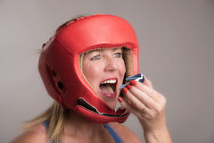 Boxer inserting a gum shield into the mouth. Female boxer wearing a safety head guard and inserting a gum shield into her mouth Royalty Free Stock Images