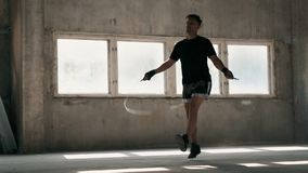 Boxer Jumps Rope. Young attractive boxer jumping rope, indoor shot in old concrete building on typical weekday stock video