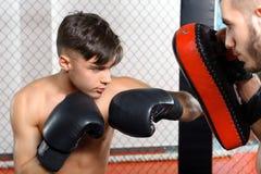 Boxer kicks punching pad Stock Photos