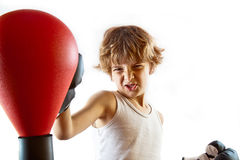 Boxer kid training. Cute kid training with punching ball and making the appropriate faces. White background, plenty of copyspace Royalty Free Stock Photos