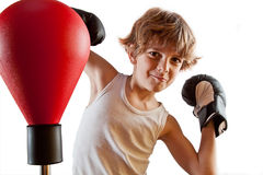 Boxer kid training with punching ball. Kid with attitude during boxing training with punching ball Stock Photos