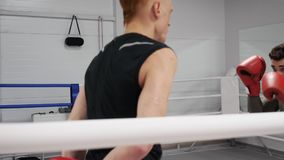 Boxer man avoiding kick whie boxing training with partner in ring. Personal trainer training boxer man at boxing ring. Boxer man avoiding kick while boxing stock video footage