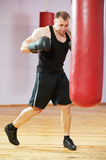 Boxer man at boxing training with heavy bag Royalty Free Stock Image
