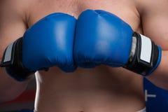 Boxer mit blauen Handschuhen in der Dunkelkammer Stockbilder