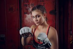 Boxer MMA female fighter posing in confident defensive stance with gloves up stock photography