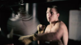 Boxer operates on a pneumatic punching bag. Athletes train impact on accuracy and speed. Boxer has an attempt on pneumatic punching bag. Young man shirtless stock video footage