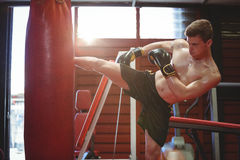 Boxer practicing kickboxing. In fitness studio Royalty Free Stock Image