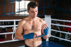 Boxer pulls bandage before the fight or training. Royalty Free Stock Photography