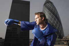 Boxer Punching Air Against Downtown Buildings Stock Photo