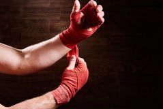 Boxer putting bandage around wrists and hands against brown wall. Royalty Free Stock Image