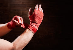 Boxer putting bandage around wrists and hands against brown wall. Royalty Free Stock Photos