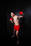 Boxer with red gloves in dark room Royalty Free Stock Photo