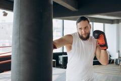 Boxer schlägt Sandsack in der Turnhalle in der Zeitlupe Junger Mann, der zuhause ausbildet Starker Athlet in der Turnhalle Getren lizenzfreie stockbilder