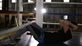 Boxer sitting on the floor at the boxing ring training abdominal muscles. Lifting torso up to the boxing ropes. Training