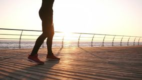 Boxer standing in front the the sunrise above the sea on the wooden floor doing exercises legs. Endurance training for a. Boxer, you only see the feet stock video footage