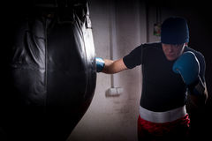 Boxer with stern look in a hat and boxing gloves training with b. Oxing punching bag in a gym Royalty Free Stock Image