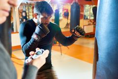 Boxer training with coach setting timer. Side view of trainer with timer watching bearded men boxing with bag in modern gym Royalty Free Stock Photography