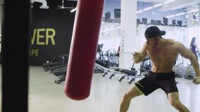 Boxer training punching bag. In fitness studio stock footage