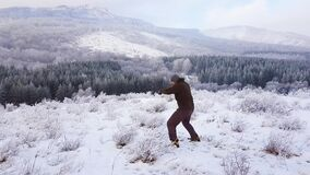 A boxer trains in the mountains in the fresh air. He works blows through the air. A fight with a shadow.