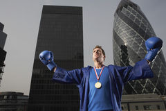 Boxer Wearing Gold Medal Against Downtown Skyscrapers Stock Photos