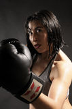 Boxer woman hiting / in gray background Royalty Free Stock Photography