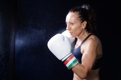 A boxer woman throws a fist. Fist in the sack. Stock Photography