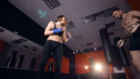A boxer woman trains with a male partner. stock video footage