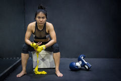 Boxer woman wearing yellow strap on wrist. Asian female boxer wearing yellow strap on wrist sitting near boxing gloves on the floor. Beautiful young woman with Royalty Free Stock Photo