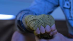 Boxer wrapping bandages on his hand before fight. Close up. Man ties his hands with a bandage.  Royalty Free Stock Image