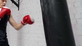 Boxermann in den Handschuhen, die Schläge auf Kampftasche während Verpackentraining in der Turnhalle machen Porträtsportmann-Verp