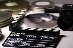 Boxes with the camera films and cinema clapper on the table. Royalty Free Stock Photography