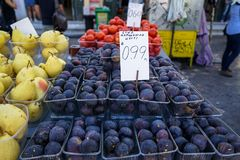 Boxes of delicious dark purple round figs, pears and tomatoes in local fruit market stall background with people Royalty Free Stock Images