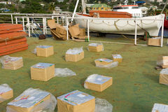 Boxes of fireworks on the deck of a ship being used for a firing platform. Imported boxes securely wrapped in plastic being placed for a fireworks display on new royalty free stock photography
