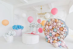 Boxes with flowers and a large pudrinitsa with balls and balloons in room decorated for birthday party. Royalty Free Stock Photography
