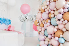 Boxes with flowers and a large pudrinitsa with balls and balloons in room decorated for birthday party. Boxes with flowers and a large pudrinitsa with balls and Royalty Free Stock Images