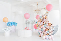 Boxes with flowers and a large pudrinitsa with balls and balloons in room decorated for birthday party. Boxes with flowers and a large pudrinitsa with balls and Stock Photos