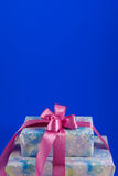 Boxes with gifts on a blue background. Two boxes with gifts tied up a pink ribbon. blue background Royalty Free Stock Image