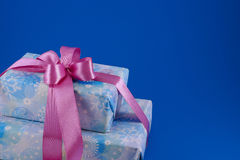 Boxes with gifts on a blue background. Two boxes with gifts tied up a pink ribbon. blue background Stock Photography