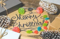 Boxes with gifts, cones, text `Merry Christmas`, candies and marmalades  on a wooden background. Boxes with gifts, cones, text `Merry Christmas`, candies and Royalty Free Stock Image