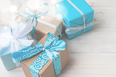 Boxes with gifts decorated with ribbons on a white wooden backgr. Four gift boxes in wrapping paper with ribbons lying on a white wooden background, selective Stock Images